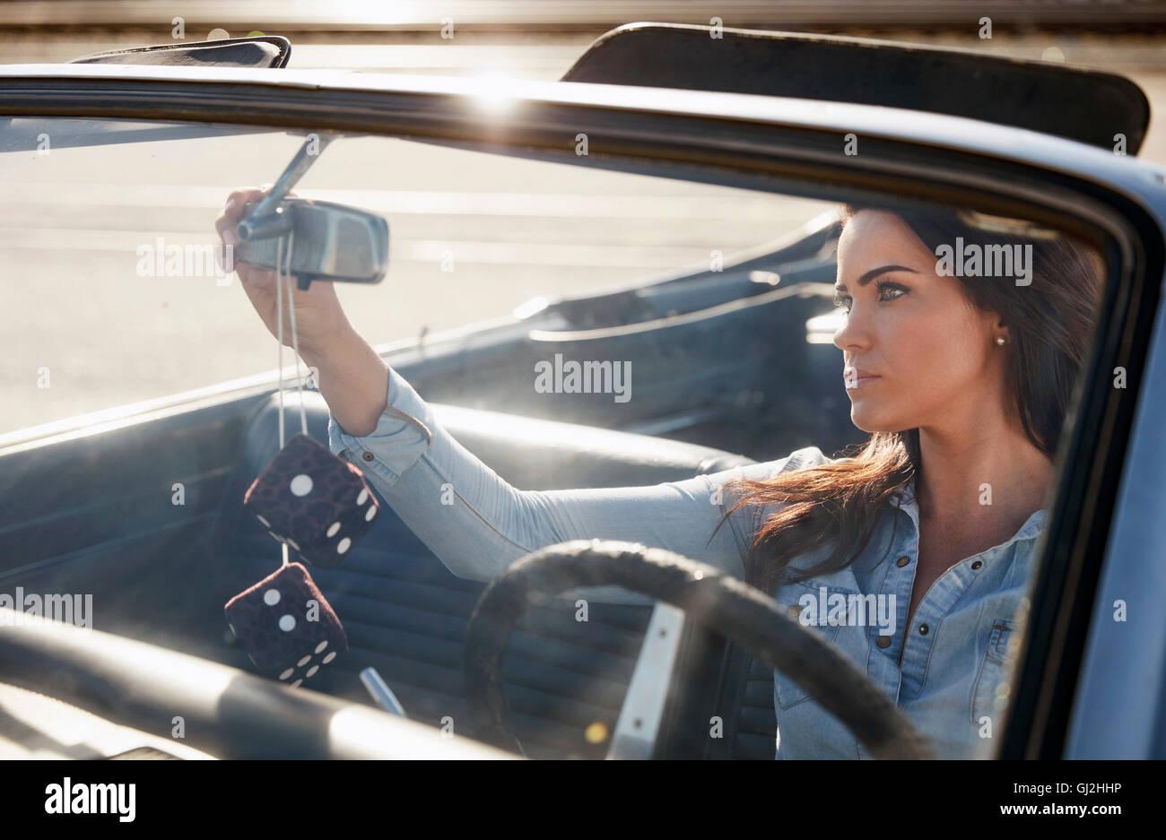 Woman in convertible car adjusting rear view mirror, Los Angeles, California, USA - Stock Image
