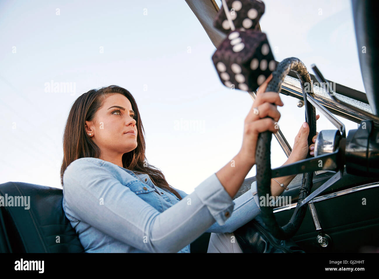 Low angle view of woman driving convertible car, Los Angeles, California, USA - Stock Image