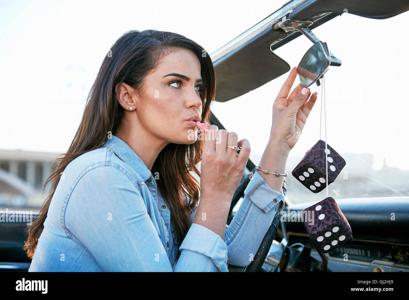 Woman in convertible car applying lipstick in rear view mirror, Los Angeles, California, USA - Stock Image
