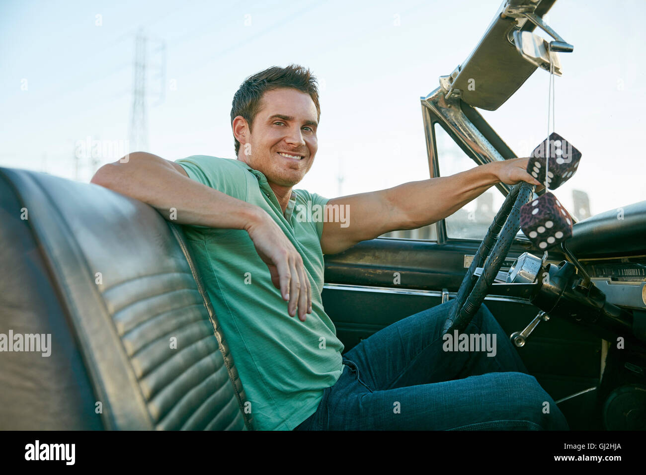 Man in convertible car looking at camera smiling, Los Angeles, California, USA - Stock Image