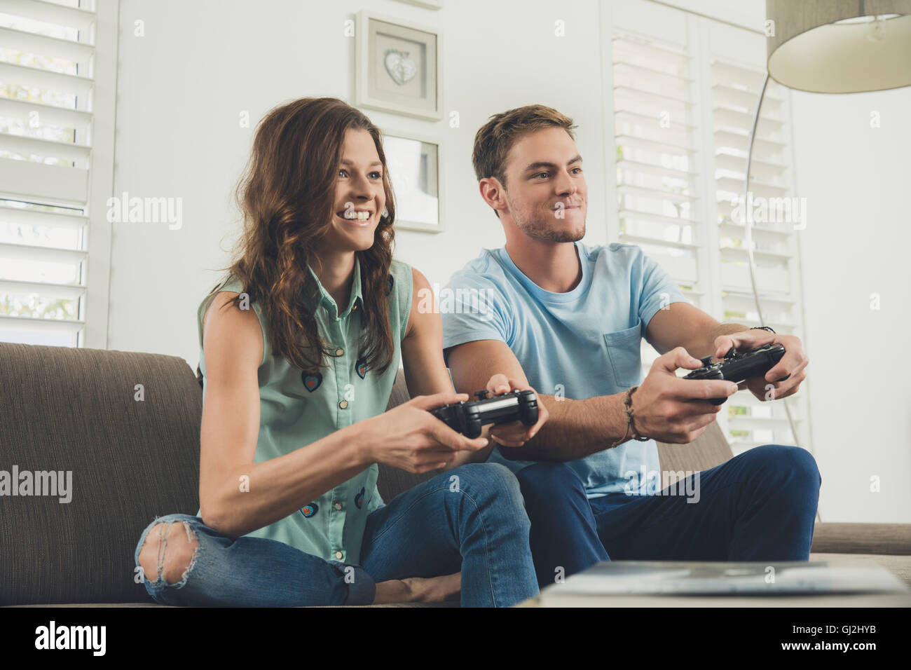 Couple on sofa using video game controller smiling - Stock Image