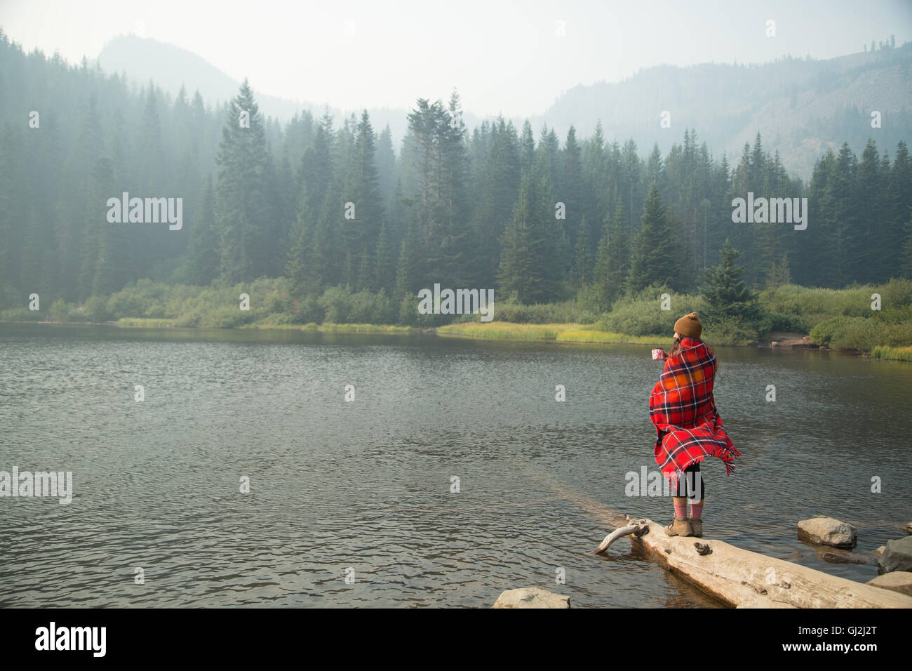 Woman wrapped in tartan blanket drinking coffee by misty lake, Mount Hood National Forest, Oregon, USA - Stock Image