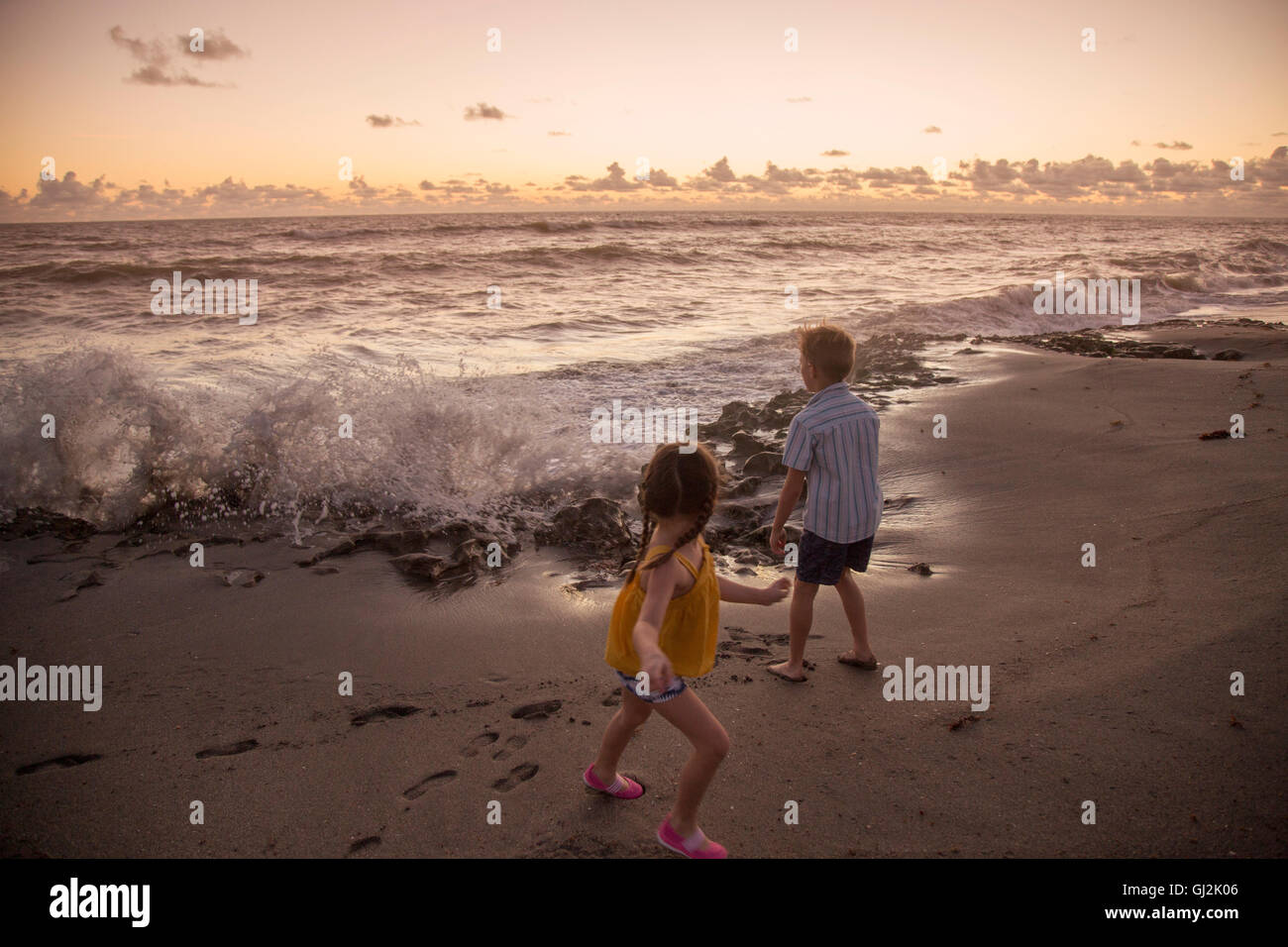 Boy and sister running away from splashing waves on beach at sunrise, Blowing Rocks Preserve, Jupiter Island, Florida, Stock Photo