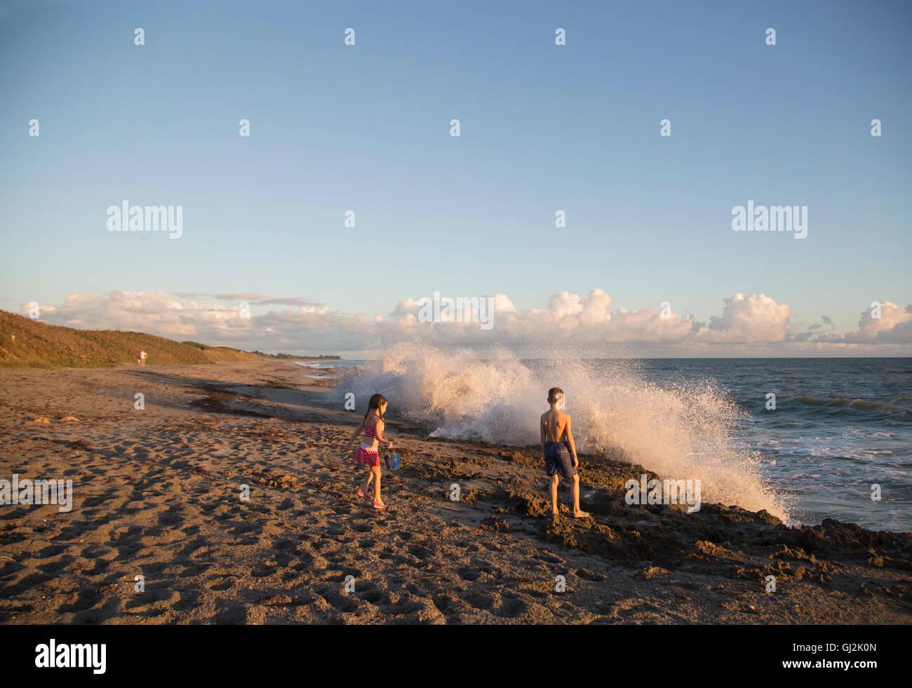Boy and sister watching splashing waves from beach, Blowing Rocks Preserve, Jupiter Island, Florida, USA Stock Photo