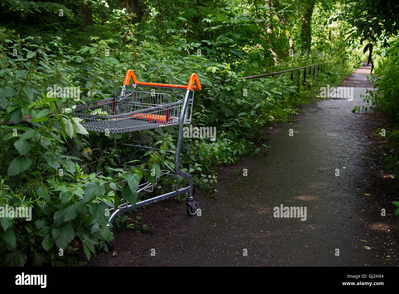 Abandoned supermarket trolley on the cyclepath in Edinburgh. - Stock Image