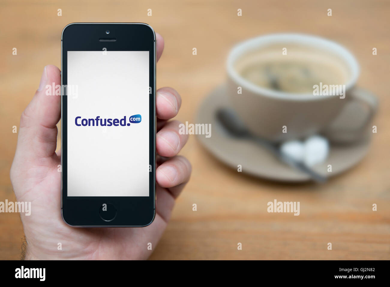 A man looks at his iPhone which displays the Confused.com logo, while sat with a cup of coffee (Editorial use only). - Stock Image