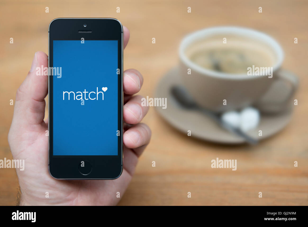A man looks at his iPhone which displays the Match logo, while sat with a cup of coffee (Editorial use only). - Stock Image
