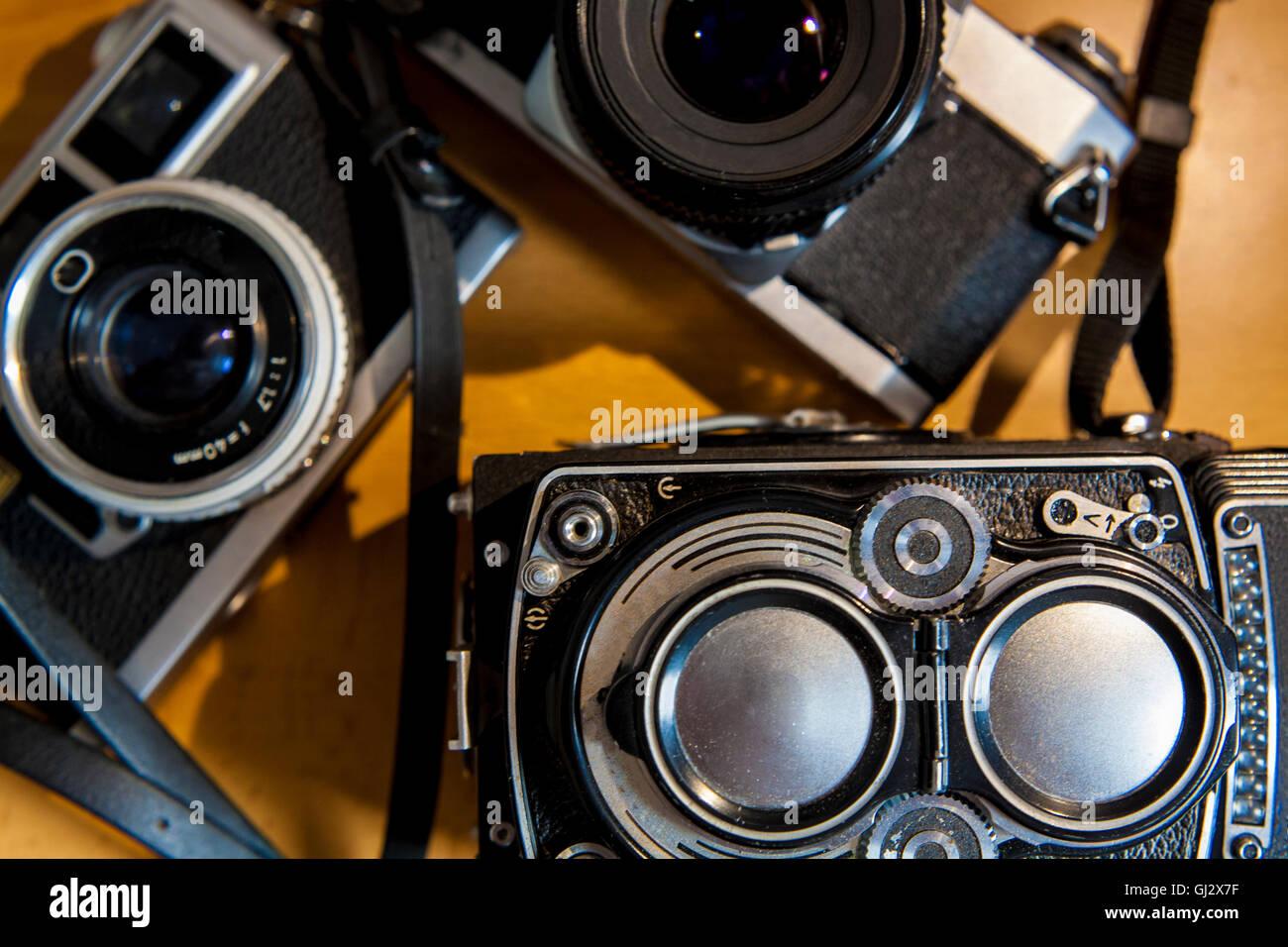 Old film SLR and TLR cameras over wooden background - Stock Image