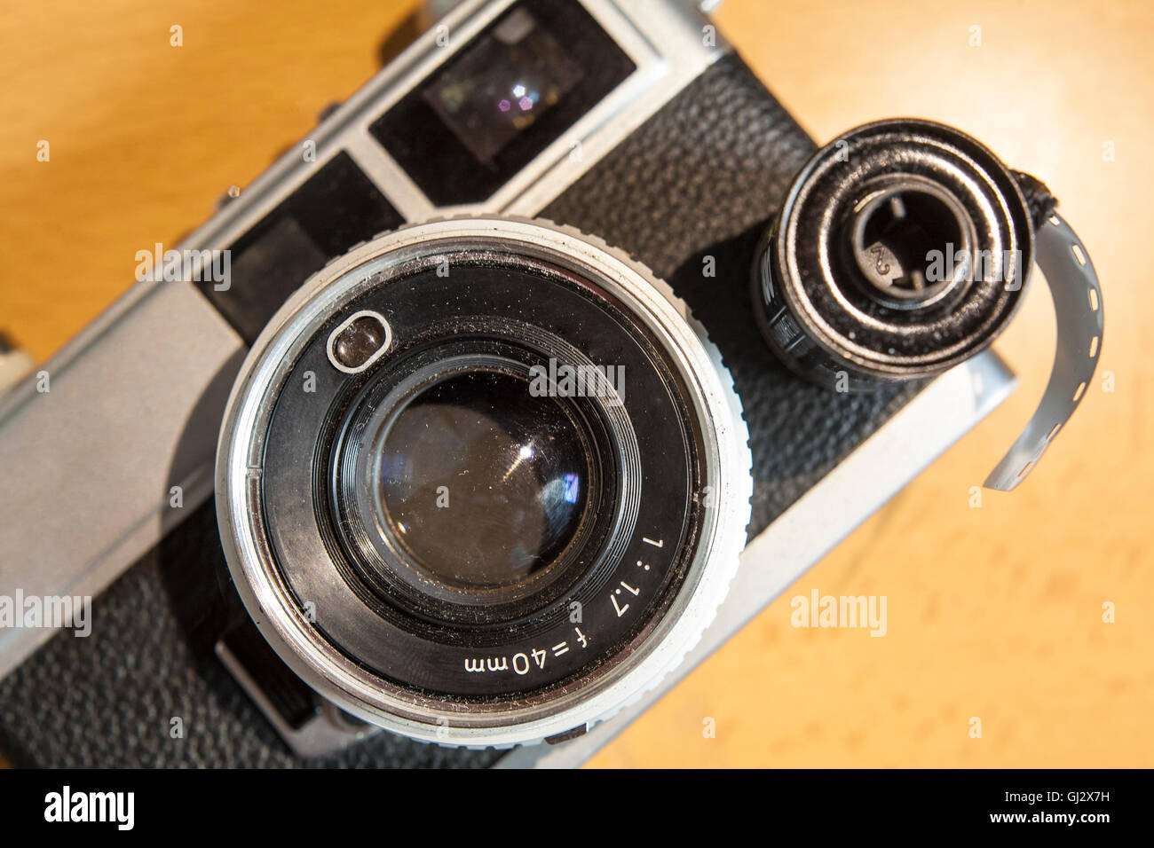 Antique SLR or Reflex camera with film roll over wooden surface - Stock Image