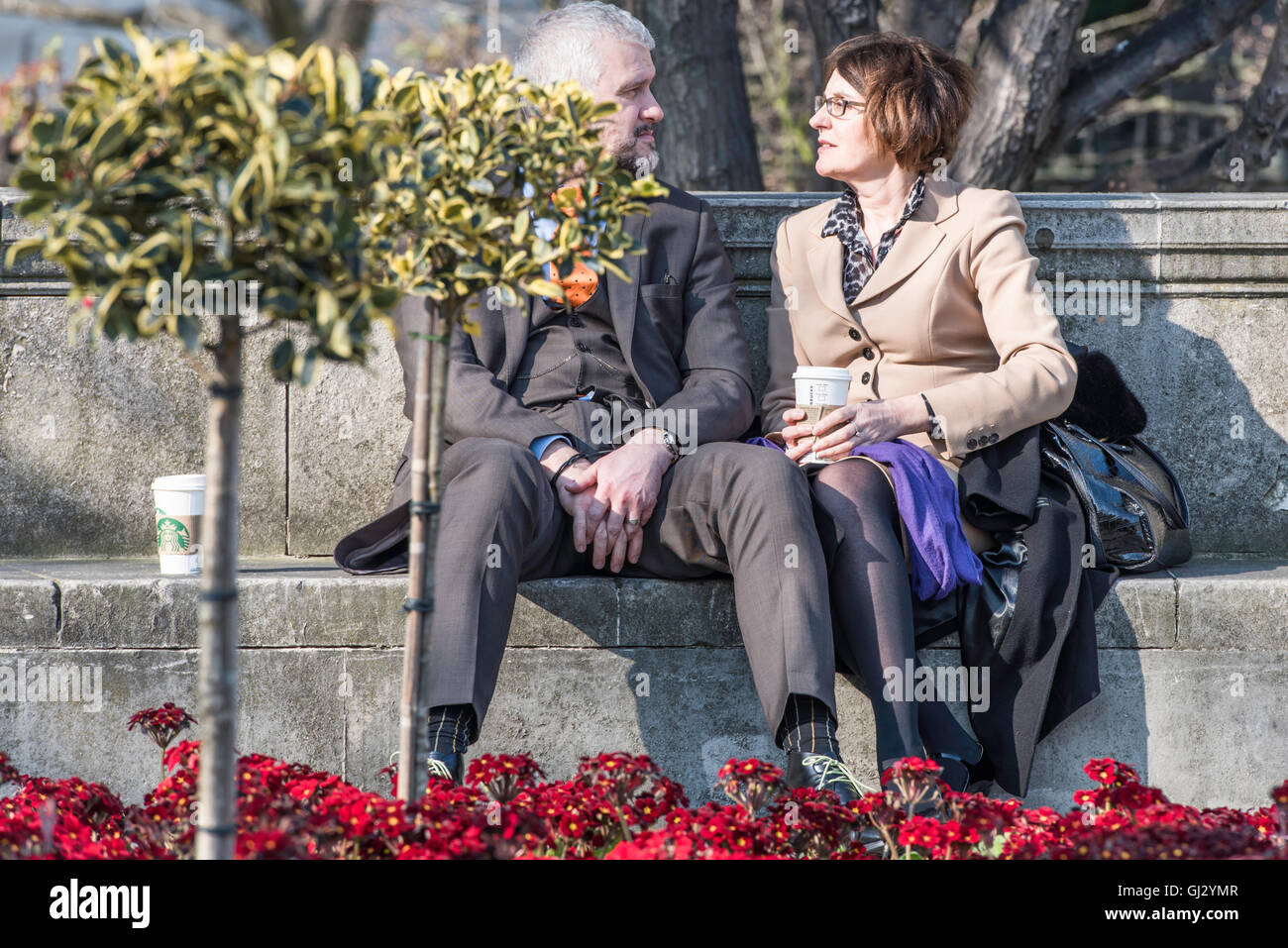 A couple, wearing suits, looking into each other's eyes and  talking intimately, as they sit in the sunshine - Stock Image