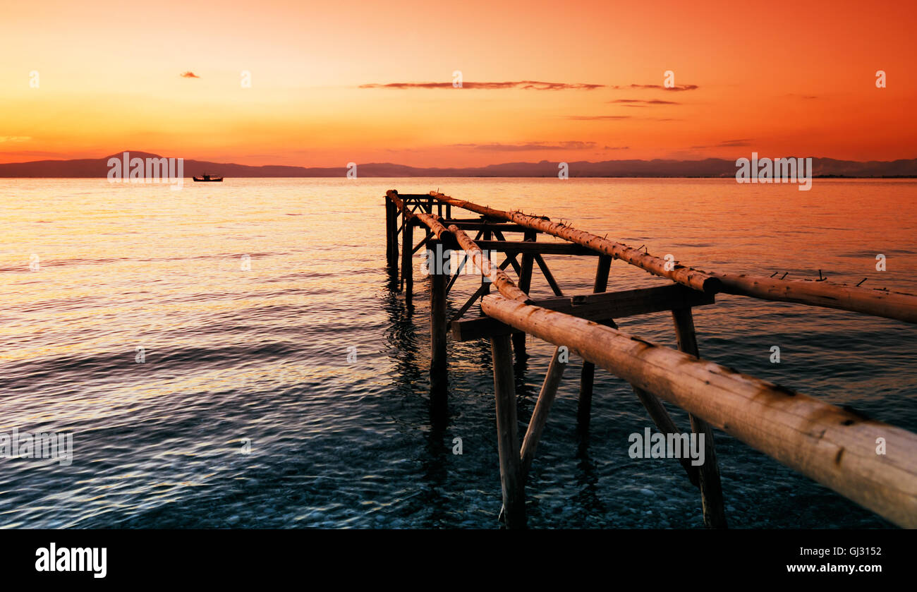 Primitive wooden pier at sunset - Stock Image