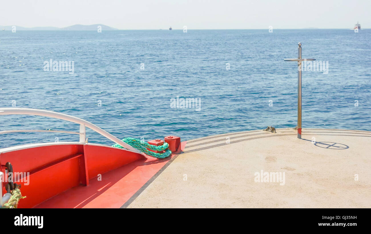 High angled, front view over the red colored deck of the saling boat on the blue ocean with the Island in front - Stock Image