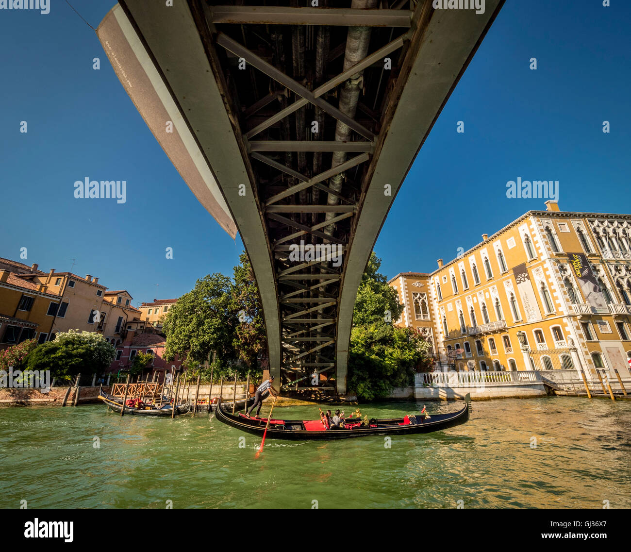 Gondola on the Grand Canal in Venice, Italy passing underneath the Accademia Bridge. Stock Photo