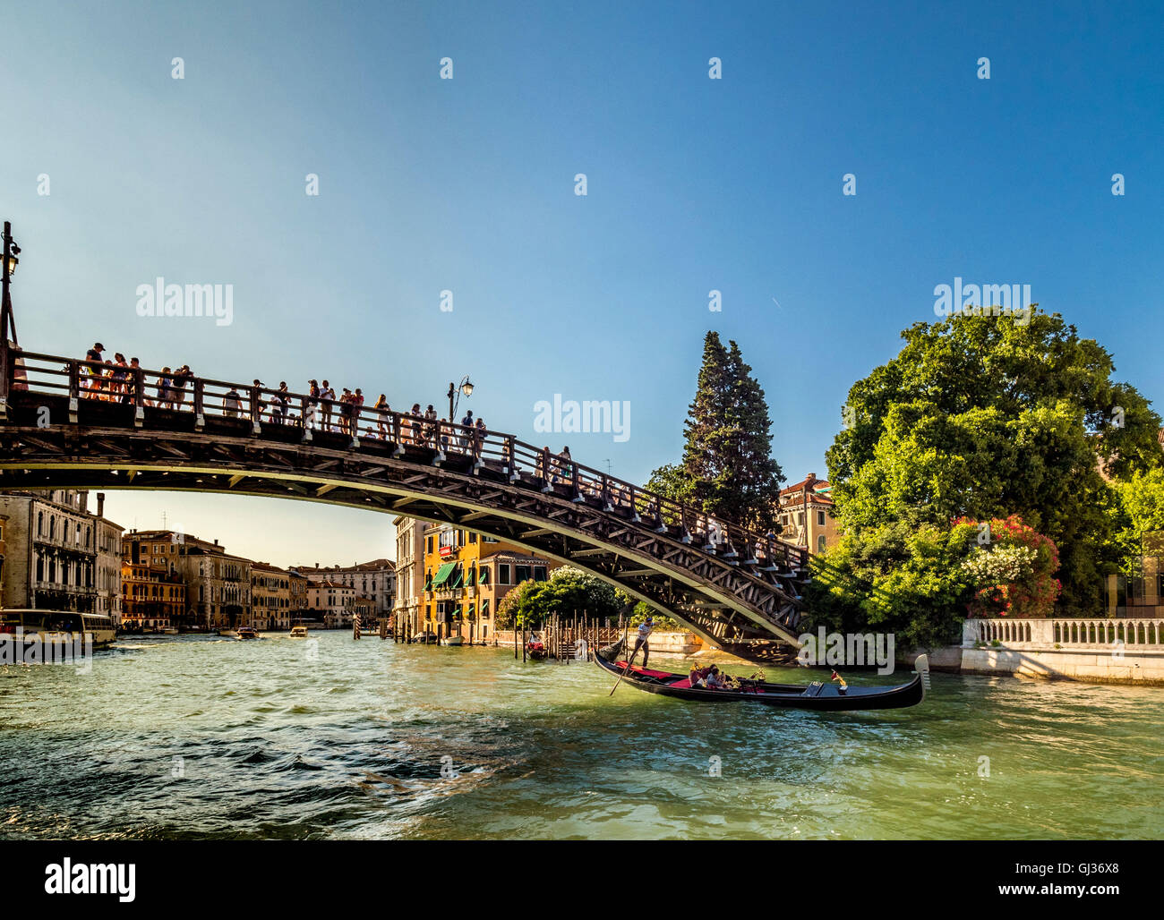 Gondola on the Grand Canal in Venice, Italy, passing underneath the Accademia Bridge. - Stock Image