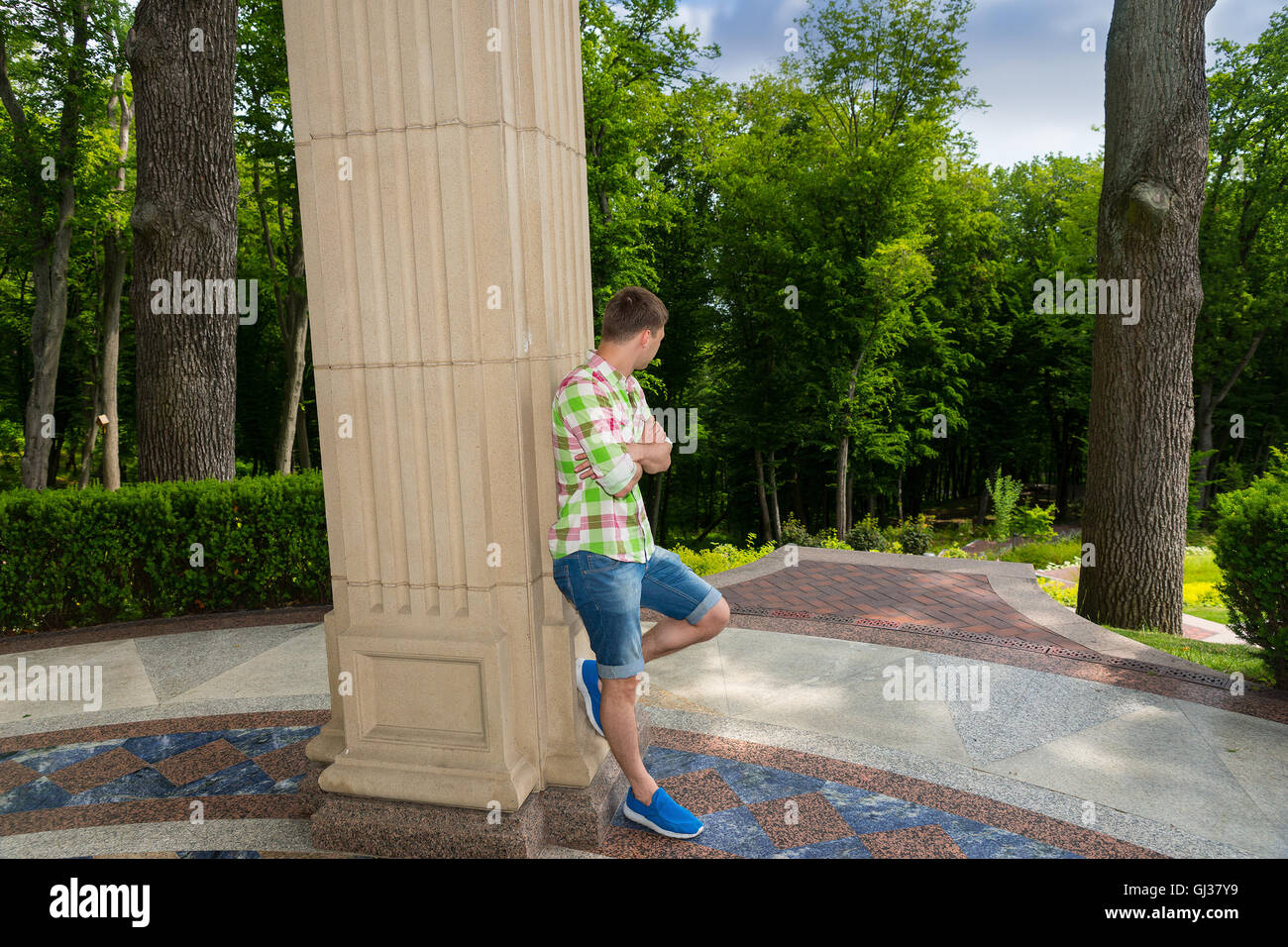 Side view on contemplative young male standing near stone wall outside facing trees in park or yard - Stock Image