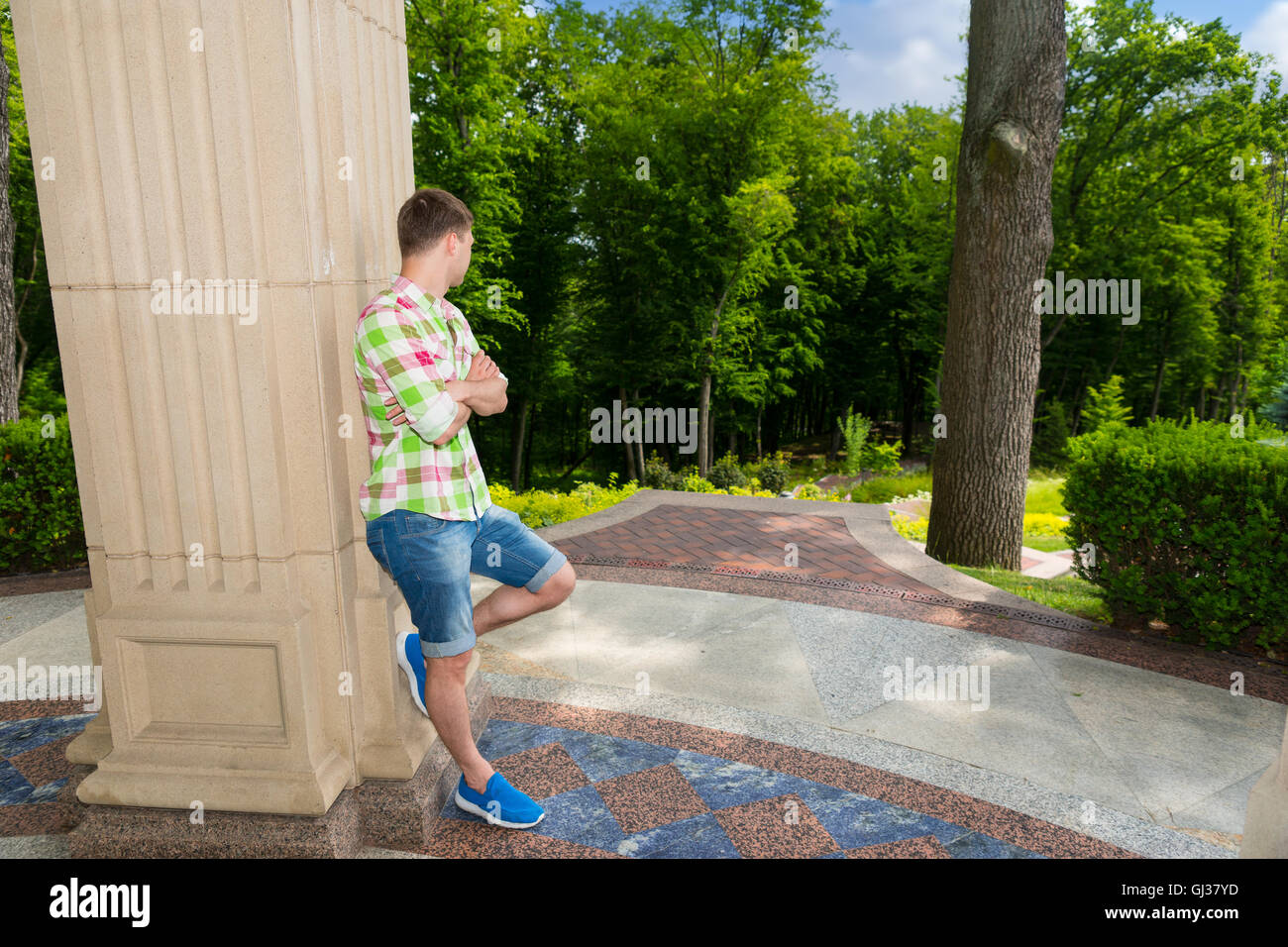 Side view on contemplative young adult man standing near stone wall outside facing trees in park or yard - Stock Image