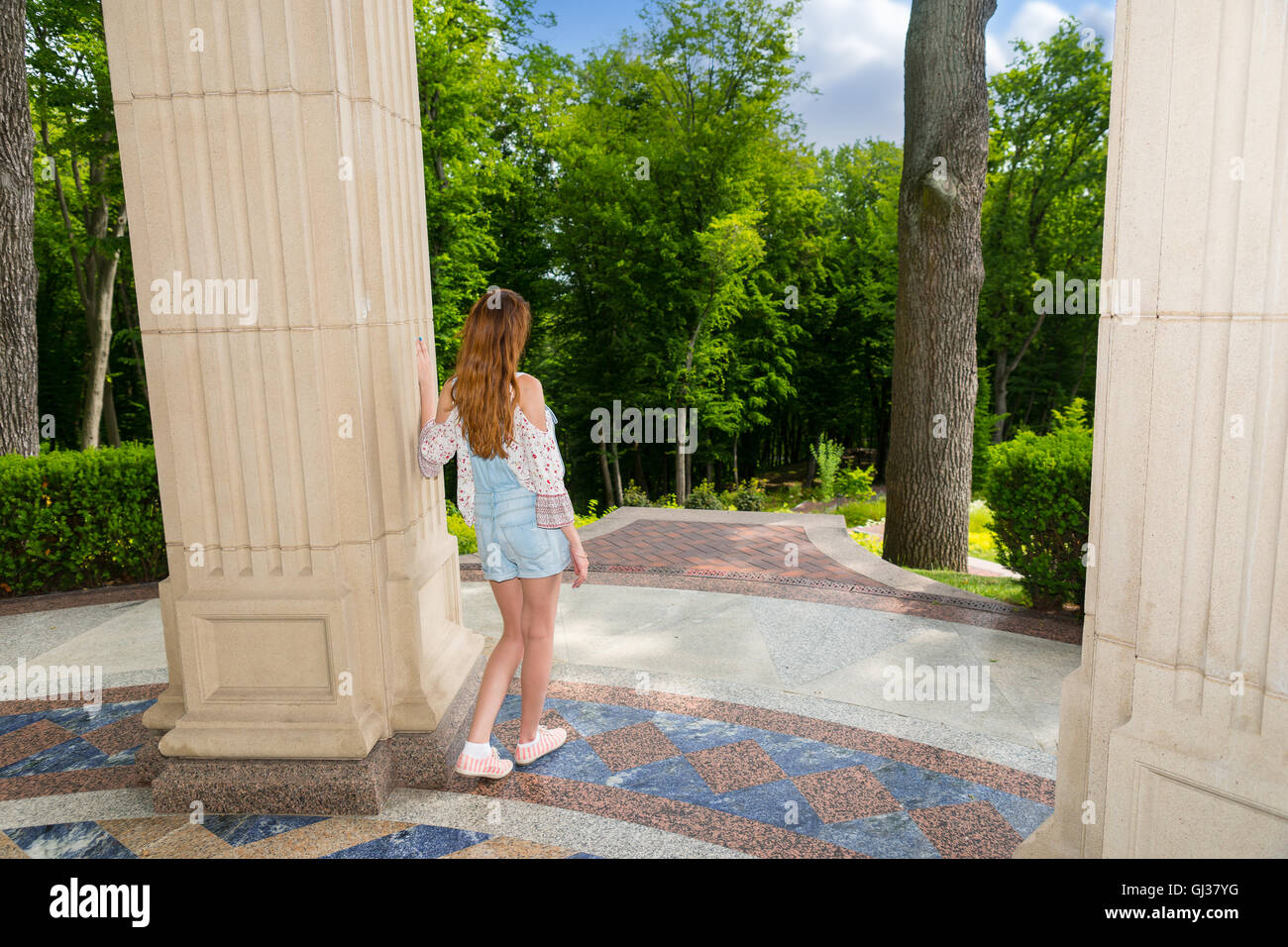 Side view on contemplative young female standing near stone wall outside facing trees in park or yard - Stock Image