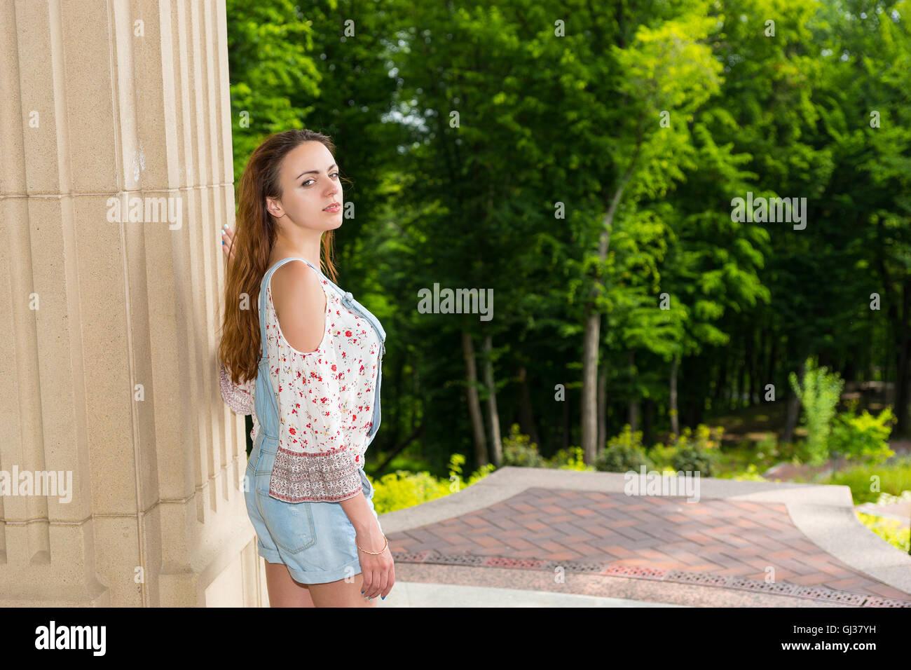 Young female turned around to look into the camera standing near stone wall outside facing trees in park or yard - Stock Image