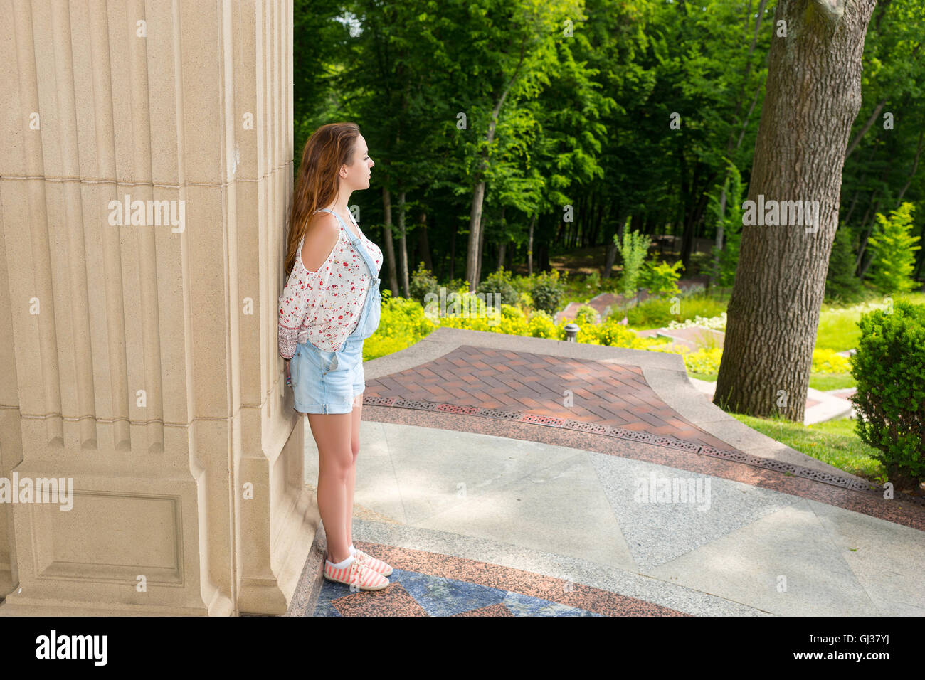 Side view on contemplative young adult woman standing near stone wall outside facing trees in park or yard - Stock Image