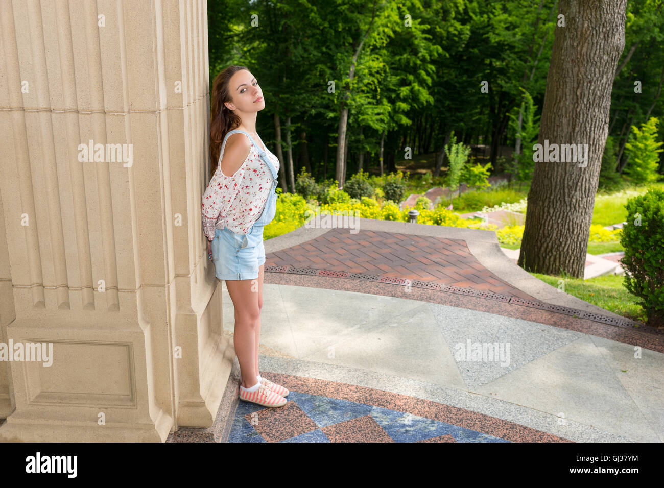 Side view on contemplative young adult woman standing near stone wall and looking into the camera outside facing - Stock Image