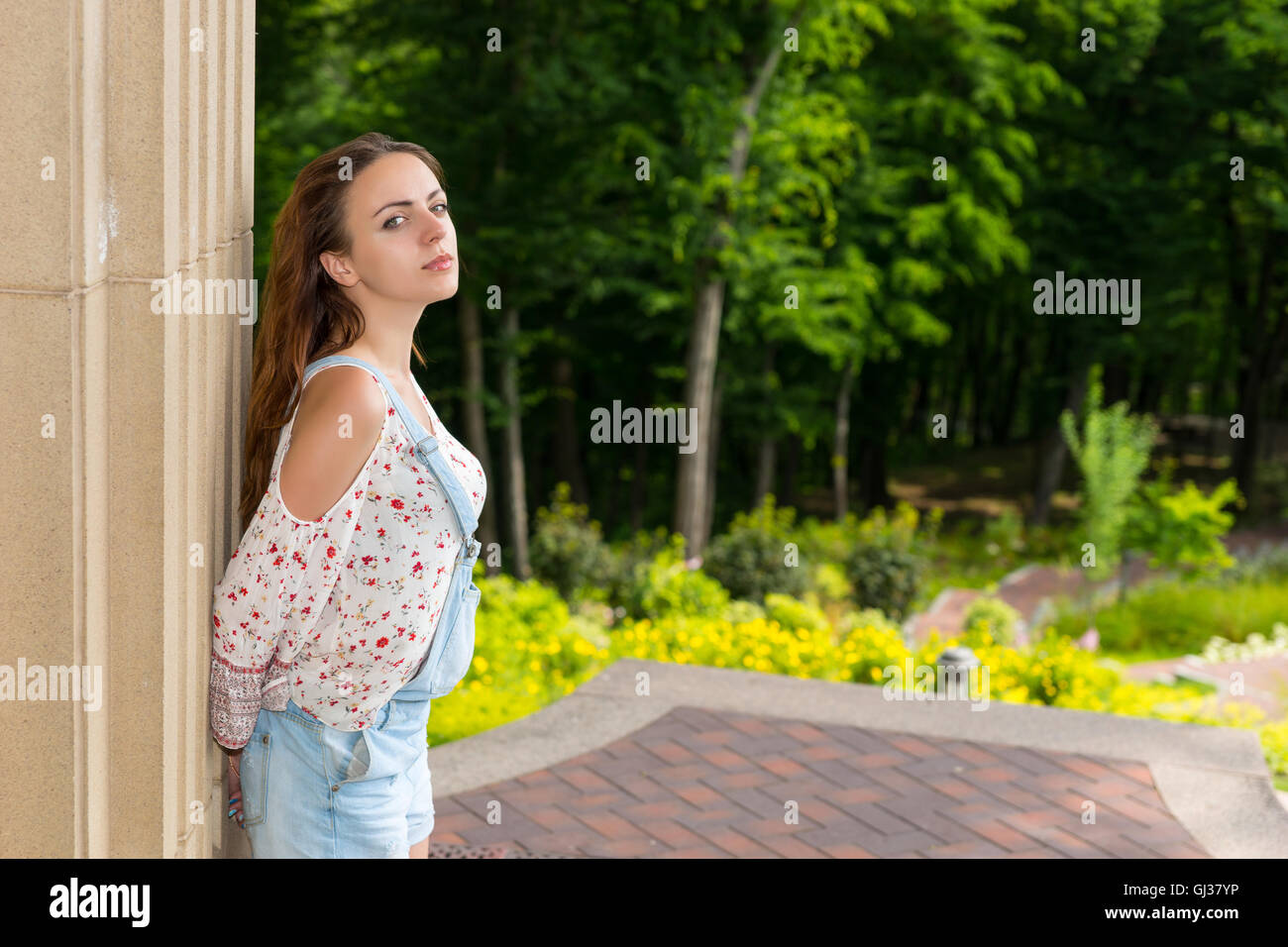 Pensive young adult woman standing near stone wall and looking into the camera outside facing trees in park or yard - Stock Image