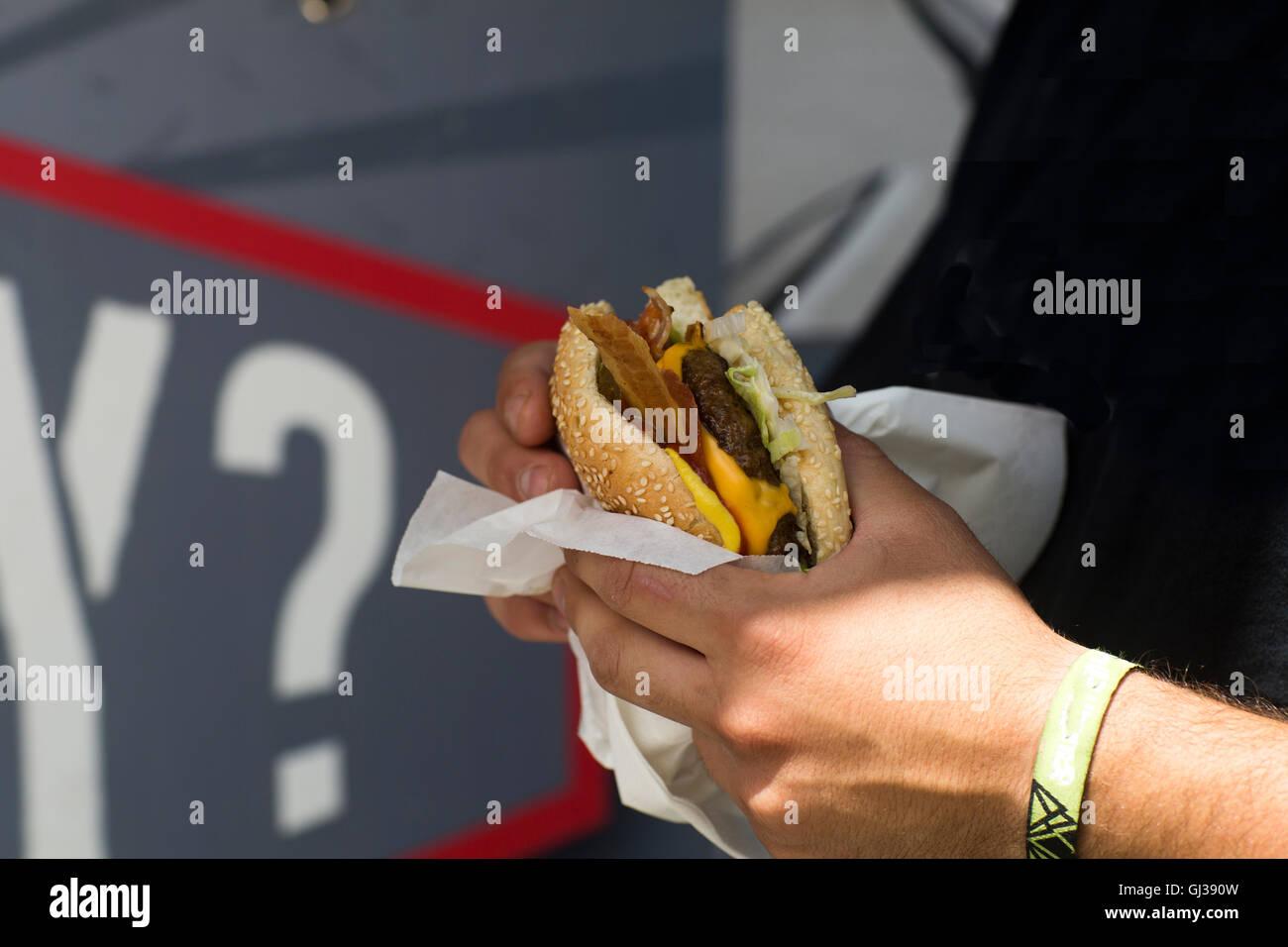 Male customer's hand eating hamburger from fast food van - Stock Image