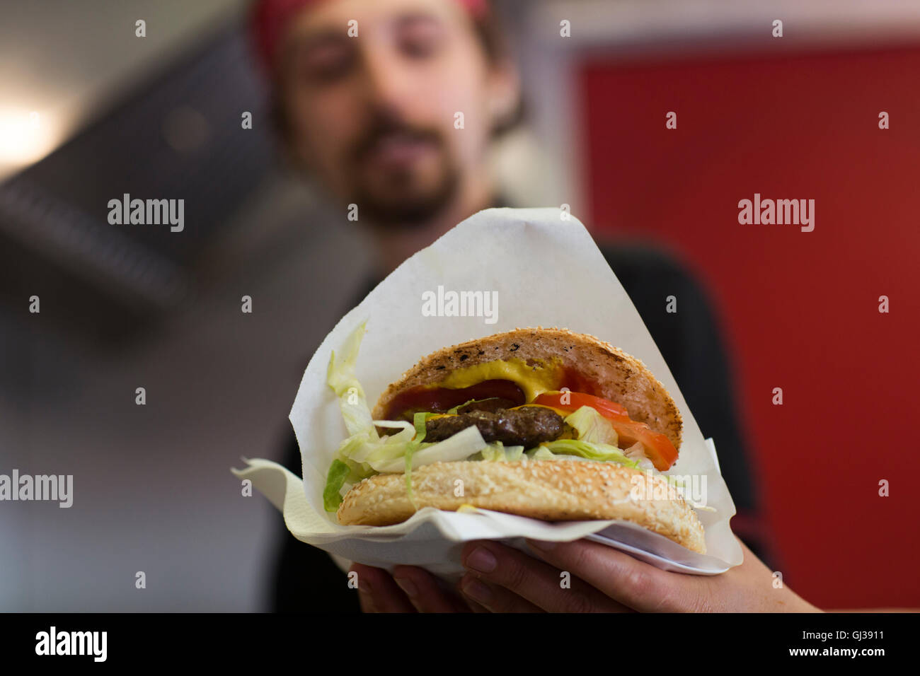 Young man serving hamburger from fast food van Stock Photo