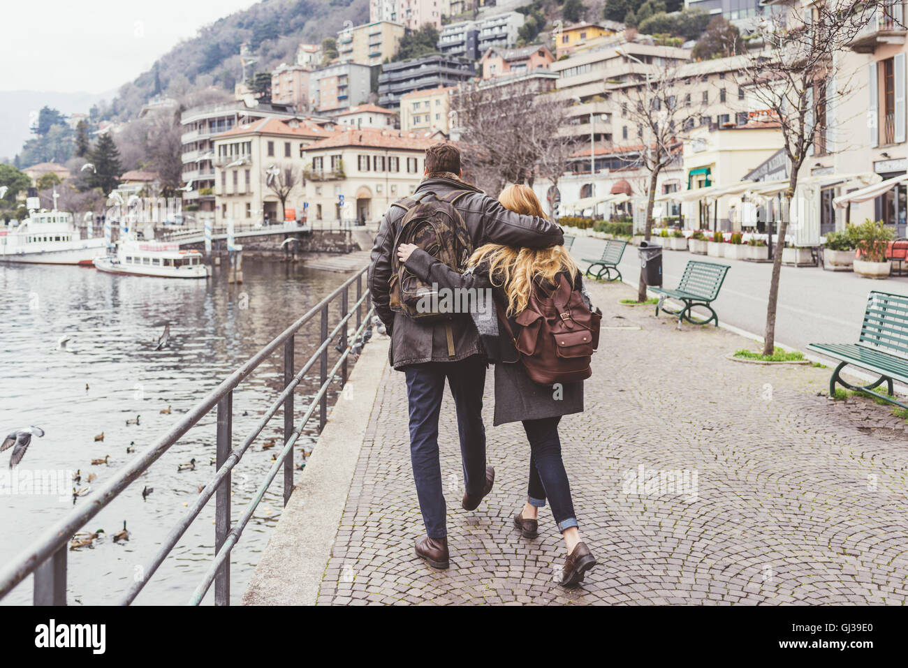 Rear view of young couple strolling along lakeside, Lake Como, Italy Stock Photo