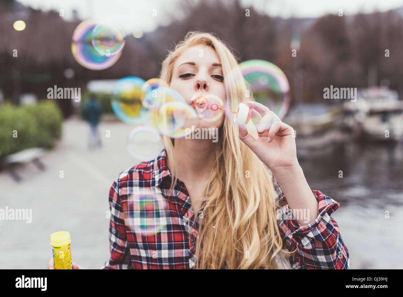 Portrait of young woman on waterfront blowing bubbles,  Lake Como, Italy - Stock Image