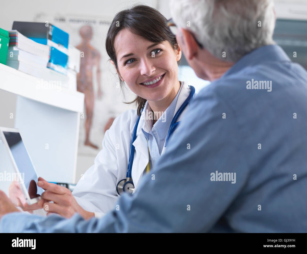 Doctor sharing health information on digital tablet with patient in clinic - Stock Image