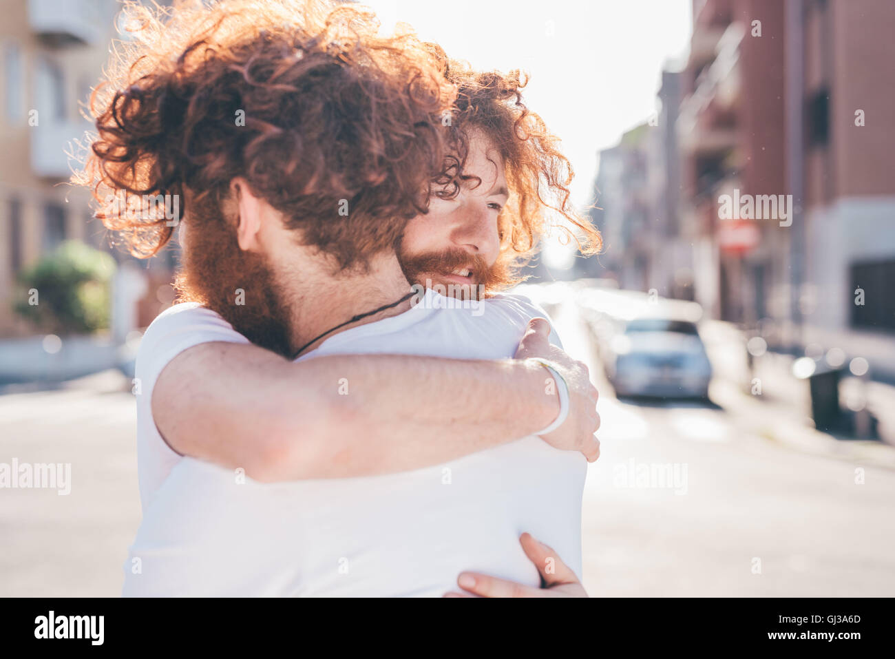 Young male hipster twins with red hair and beards hugging on city street Stock Photo