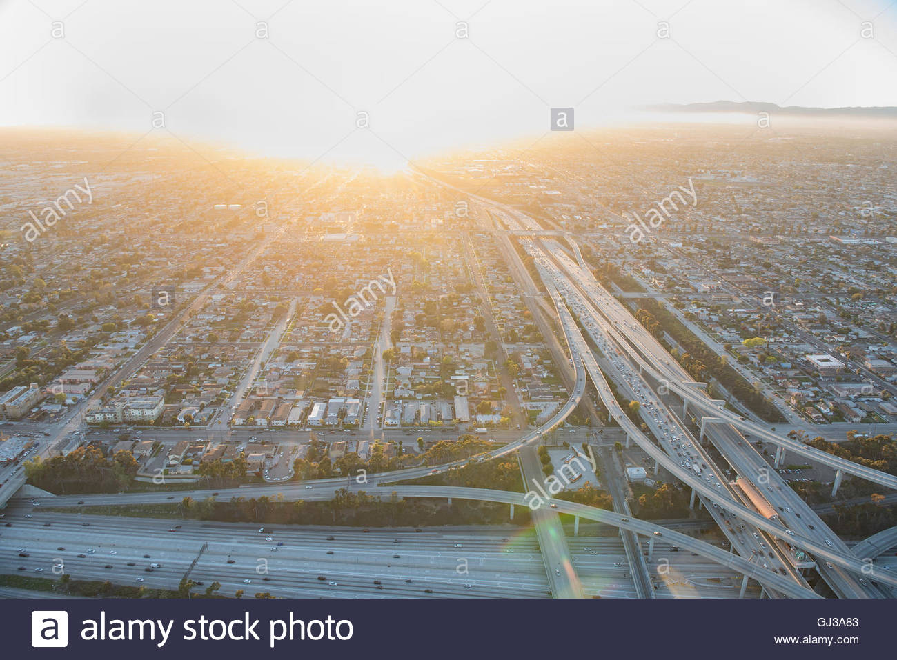 Sunlit aerial view of traffic on highway and flyover, Los Angeles, California, USA - Stock Image