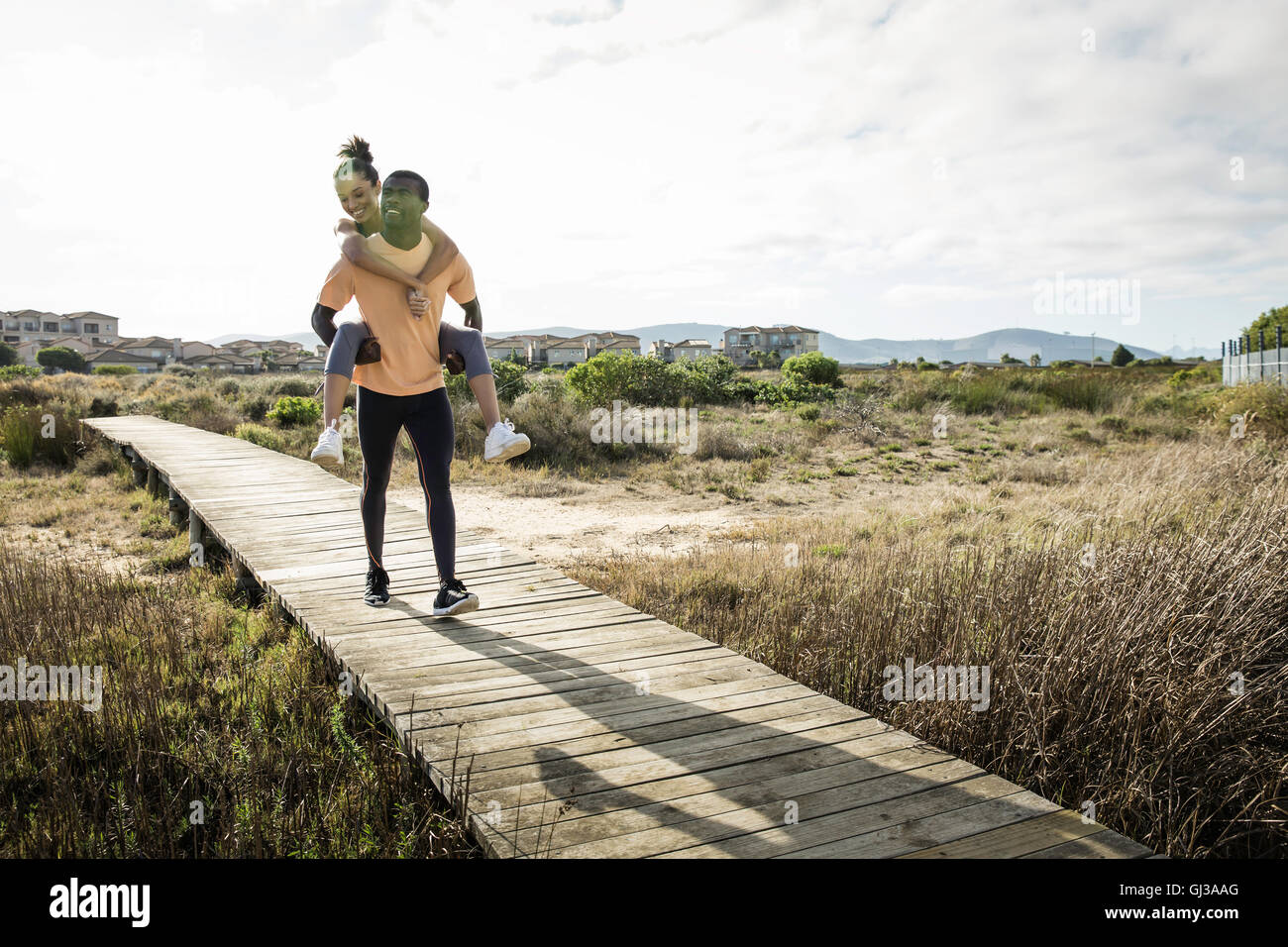Man giving friend piggyback on wooden walkway - Stock Image