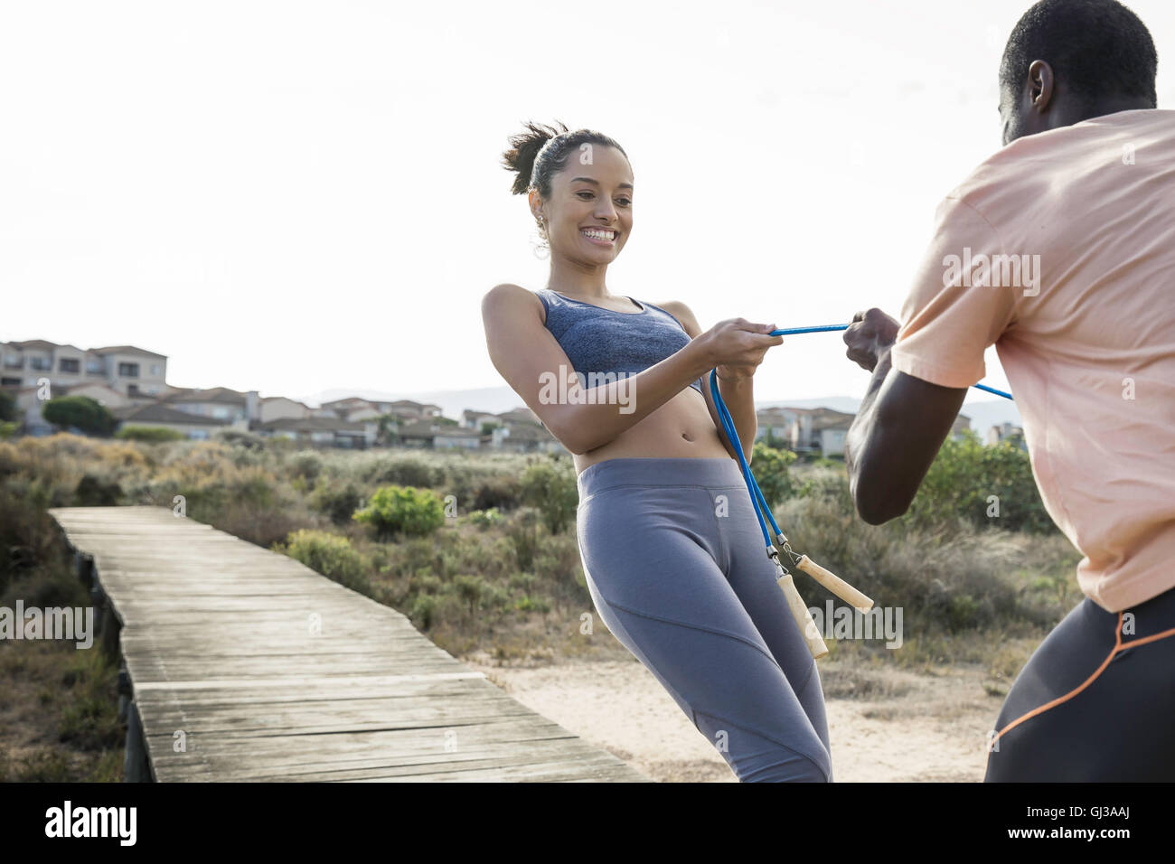 Couple tugging on skipping rope smiling - Stock Image