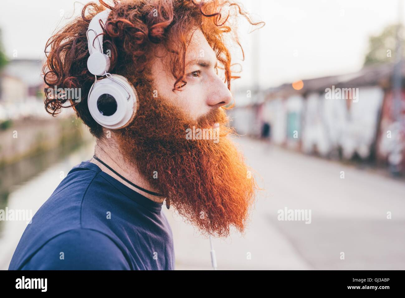 Young male hipster with red hair and beard listening to headphones in city - Stock Image