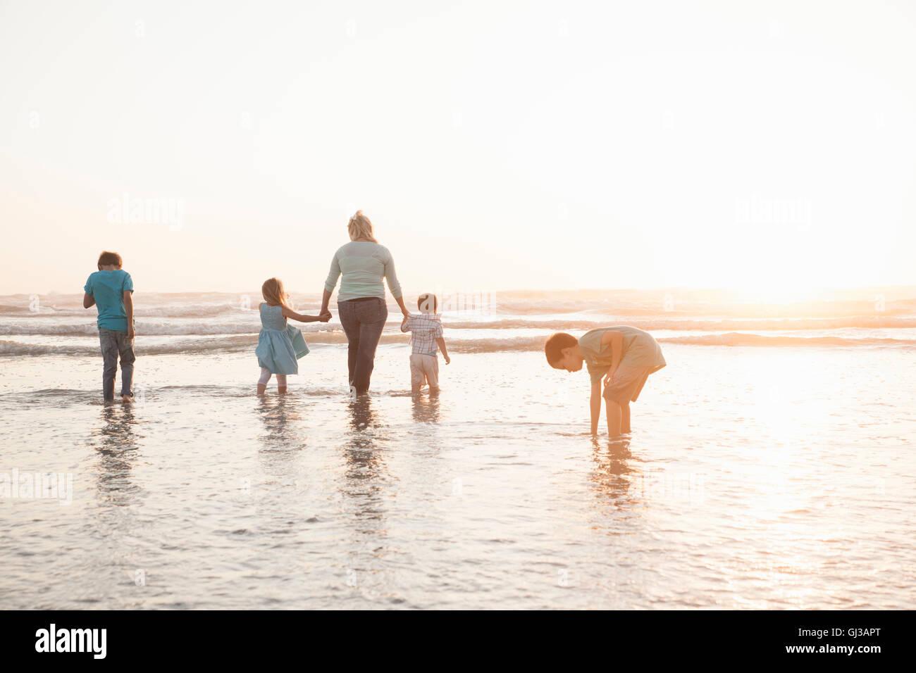 Family holding hands paddling in ocean - Stock Image