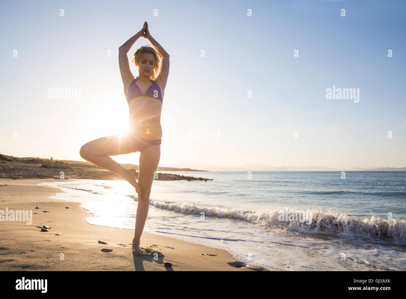 Young woman on beach, standing on one leg, in yoga position - Stock Image