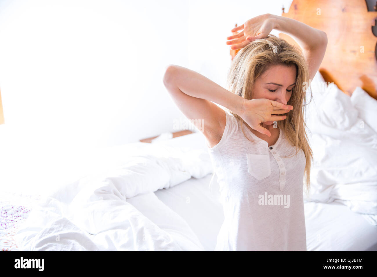 Young woman yawning in bedroom in morning - Stock Image
