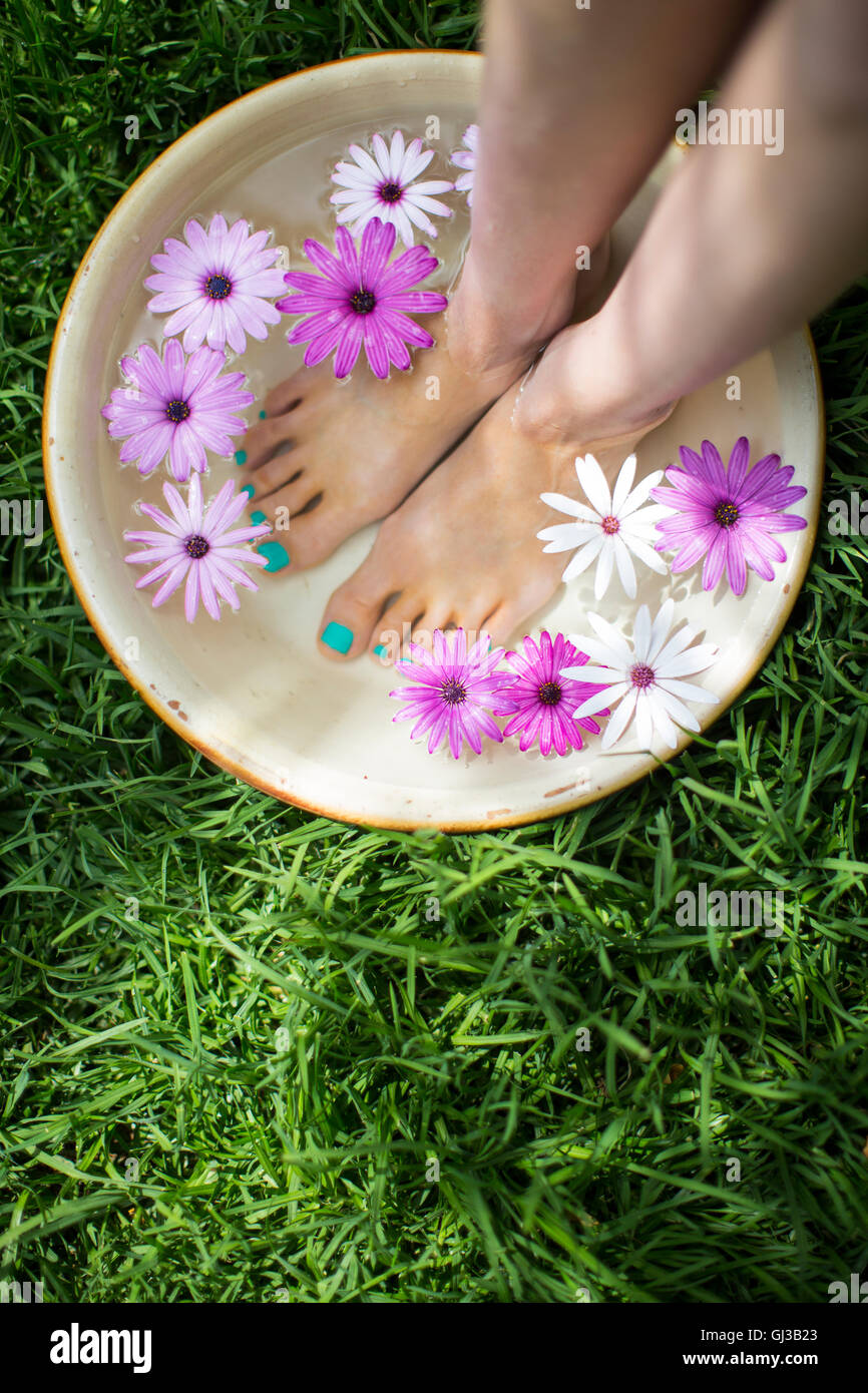 Young woman's feet in bowl of flower water on lawn - Stock Image