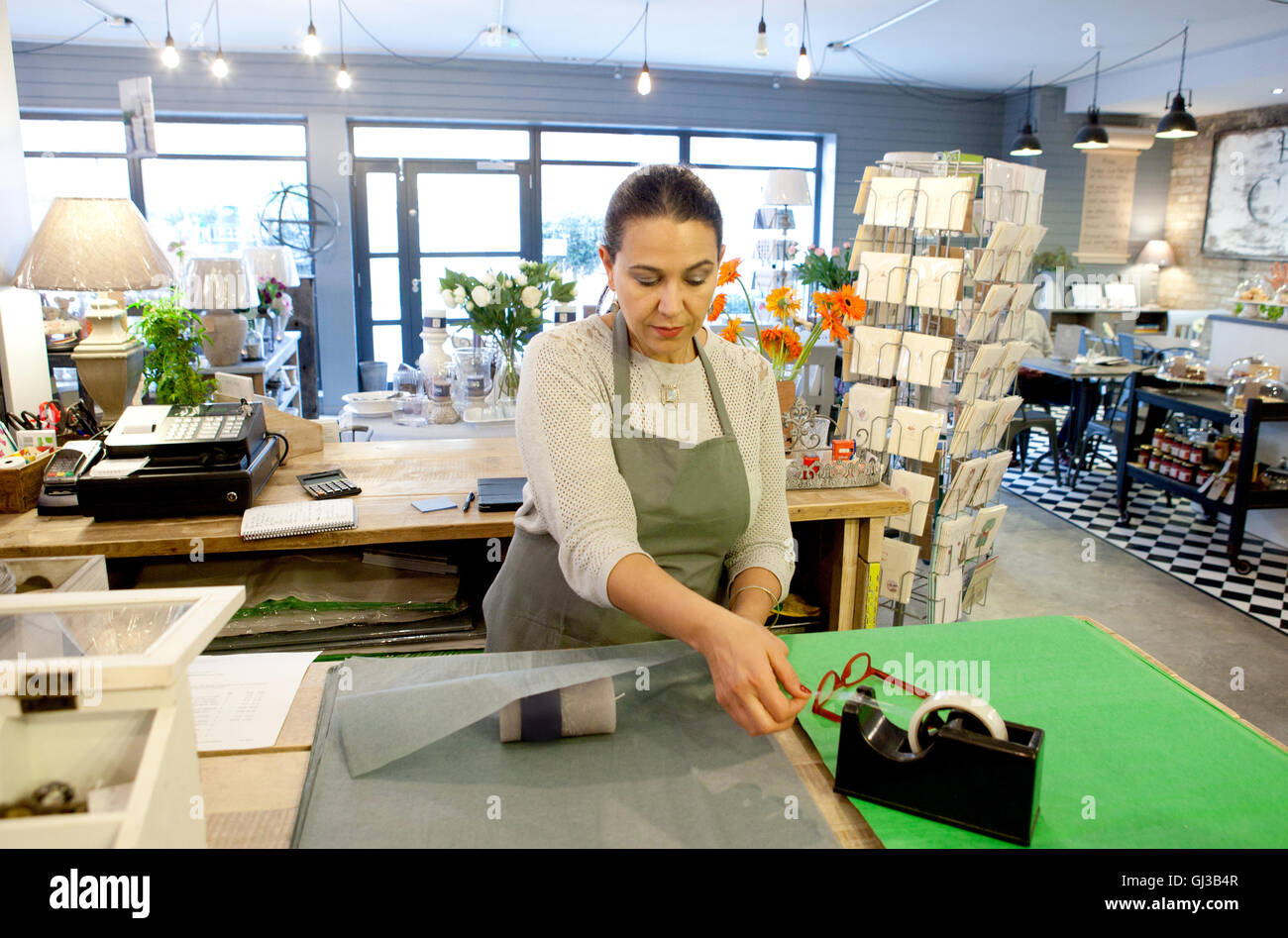 Female sales assistant wrapping candle at checkout in gift shop - Stock Image