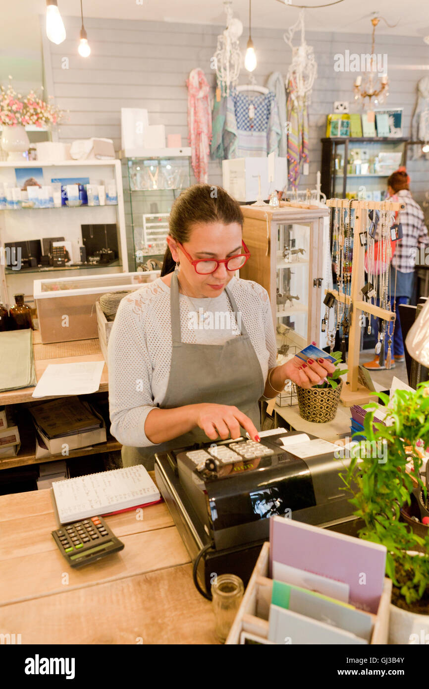 Female sales assistant using till at checkout in gift shop - Stock Image