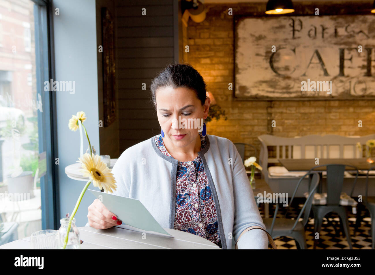 Mature female customer reading menu in cafe - Stock Image