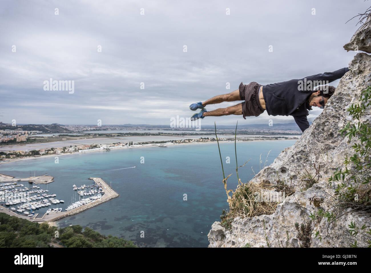 Male rock climber balancing horizontally mid air on coastal rock, Cagliari, Italy - Stock Image