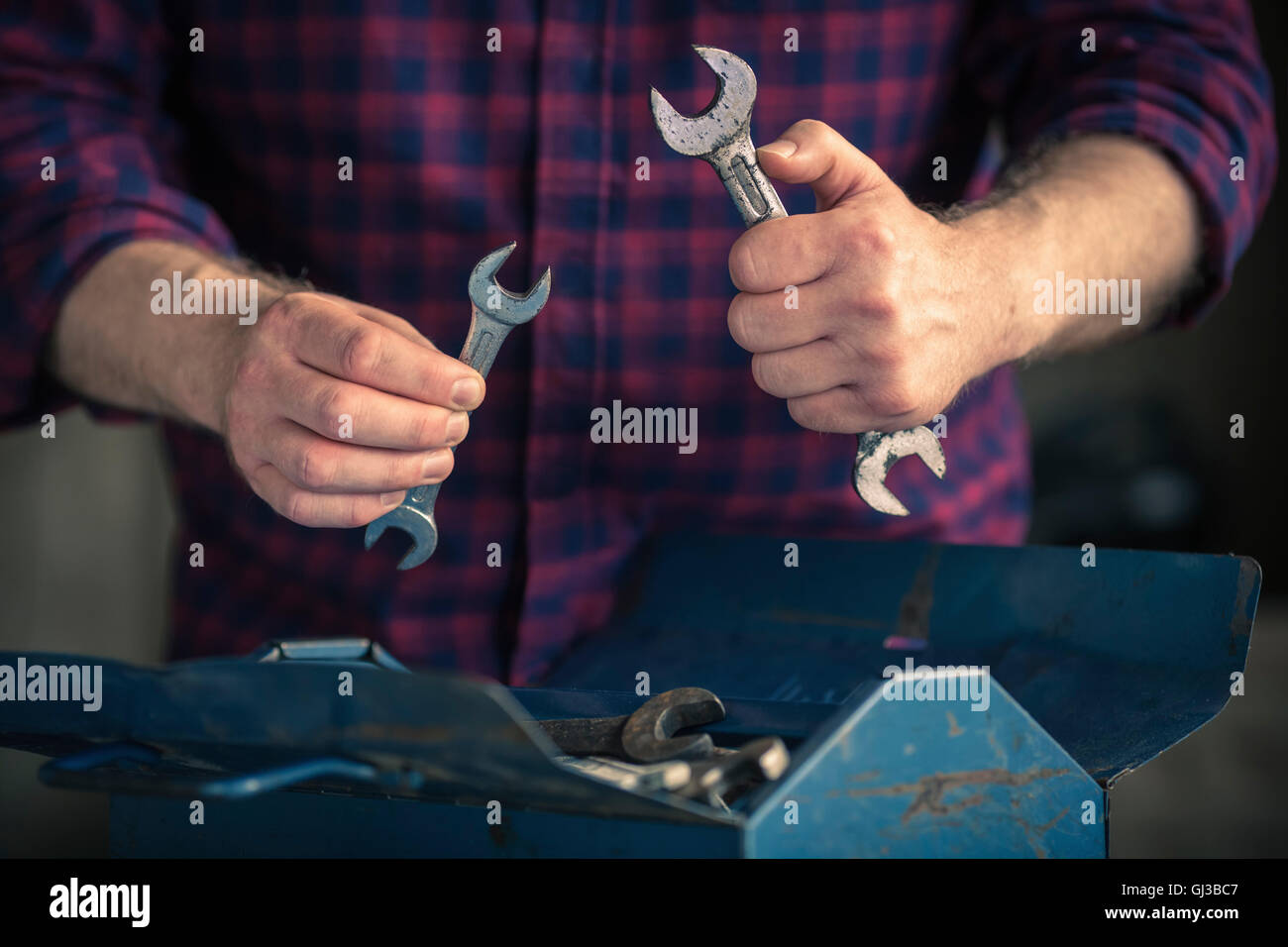Man holding different sized spanners - Stock Image