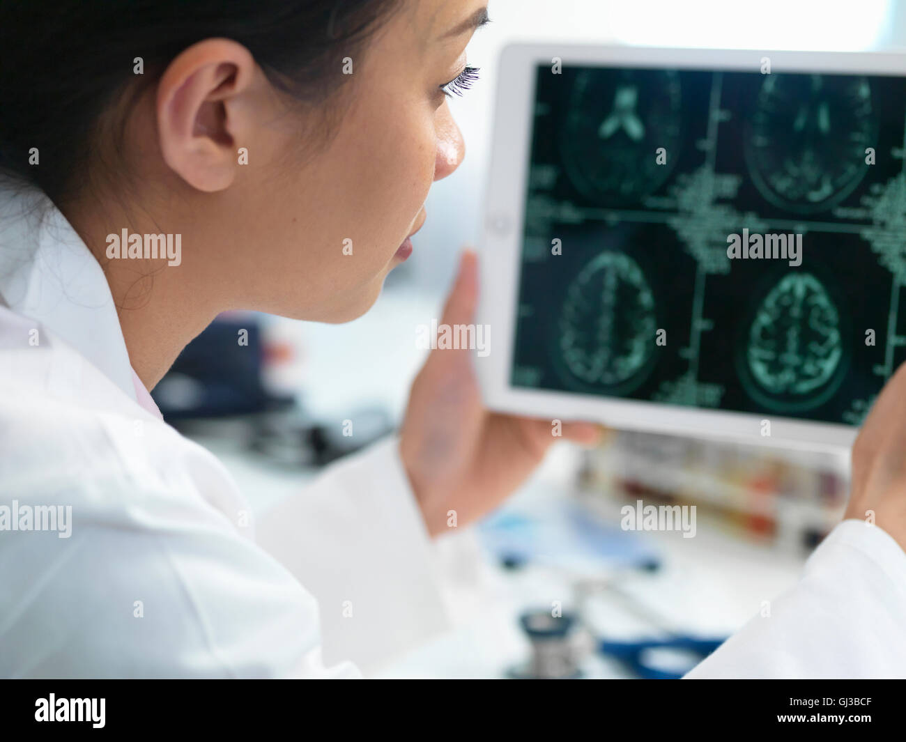 Doctor viewing CT scan result of brain on digital tablet for abnormalities - Stock Image
