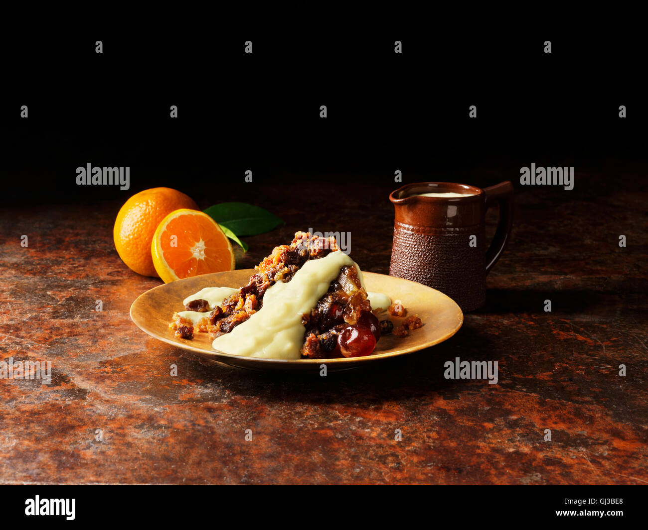 Christmas pudding with liqueur and orange sauce on gold plate, oranges, vintage pot of sauce - Stock Image