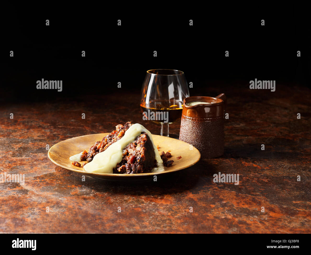 Vanilla and armagnac sauce poured over christmas pudding, glass of brandy and pot of sauce - Stock Image