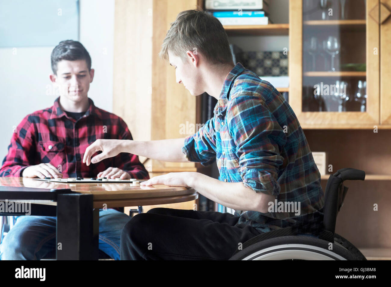 Young man using wheelchair playing draughts with friend in kitchen - Stock Image