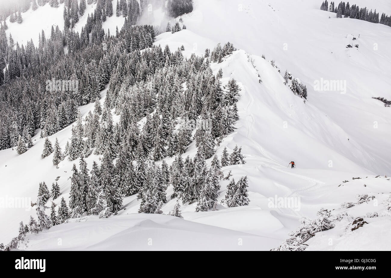Distant view of male skier walking uphill at Kranzegg, Bavaria, Germany Stock Photo
