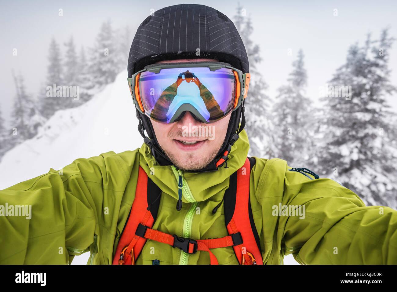 Close up of male skier wearing ski goggles taking selfie on mountain at Kranzegg, Bavaria, Germany - Stock Image